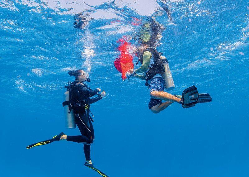 scuba divers using lift bag