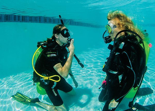 [ONE] After indicating that she is out of air, this diver signals that she needs to share air.