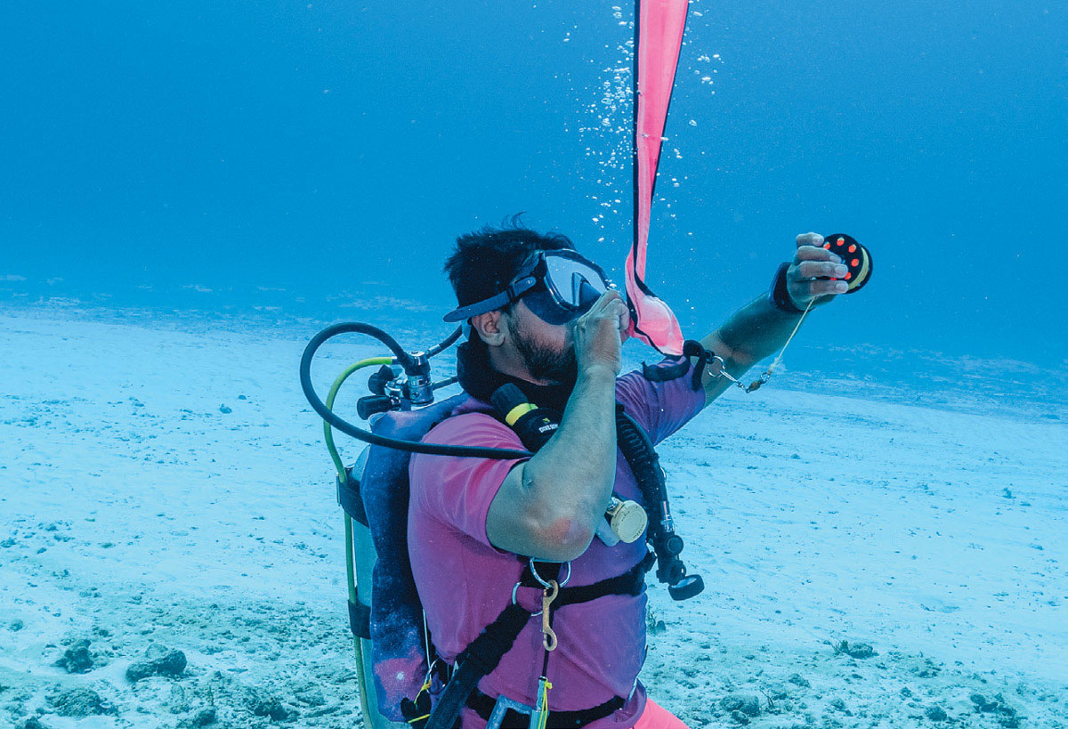 scuba diver inflating safety sausage
